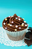 A cupcake with chocolate icing and sugar stars in a paper case on a doily, and pieces of chocolate
