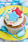 A vanilla cupcake with colourful stars, sugar confetti and blue sugared almonds
