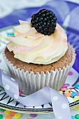 A vanilla cupcake with cream and a fresh blackberry