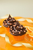 Two chocolate cupcakes with sugar confetti and oranges