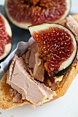 A slice of baguette with goose liver pate and figs