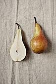 A whole pear and a pear half on a linen cloth