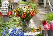 Sommerstrauss mit Dahlien, Alstroemeria und Rudbeckia auf Gartentisch