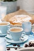 Kaffeetassen, Kaffeebohnen und süsses Gebäck