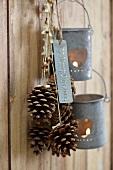 Pinienzapfen mit weihnachtlichen Bändern und Windlichter hängen auf Haken an einer Holzwand
