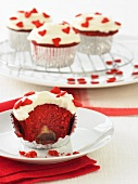 A Red Velvet Cupcake with White Frosting and Red Candy Hearts; Bitten