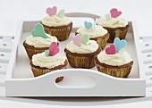 Vanilla cupcakes with glacé icing and sugar hearts on a tray