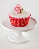 A cupcake with white glaze and a sugar rose