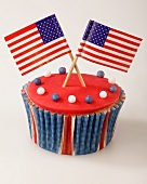 A cupcake decorated with red glaze and US flags