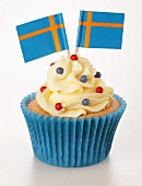 A cupcake decorated with buttercream and Swedish flags