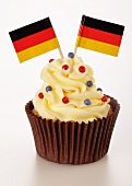 A cupcake decorated with buttercream and German flags