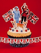 A cupcake topped with Queen Elizabeth II of England and Prince Philip, Corgis and Union Jack flags