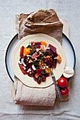 A salad of fish, tomatoes, beetroot and mandarins