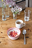 A bowl of muesli with yoghurt and a cup of coffee on a wooden table