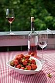 Eine Schale Erdbeeren und Rosewein auf dem Balkontisch mit karierter Tischdecke