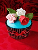 A red velvet cupcake with sugar roses