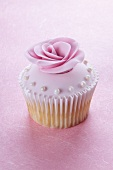 A cupcake with pink glaze, a sugar rose and sugar pearls