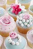 Assorted celebration cupcakes with sugar roses and sugar pearls