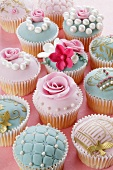 Assorted celebration cupcakes decorated with sugar roses and sugar pearls