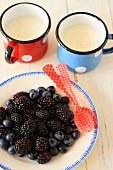 Blackberries and blueberries on a plate with two enamelled mugs of natural yoghurt