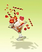 Action shot of an ice cream sundae with vanilla ice cream, lemon ice cream, cream and fresh strawberries