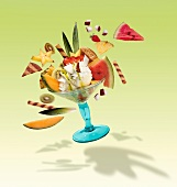 A fruit sundae with lemon ice cream, fresh fruit, cream and wafers, flying through the air