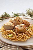 Bocconcini di tonno (bite-sized chunks of tuna, Italy) with sesame seeds, on spaghetti