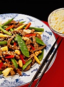 Strips of beef with sugar snap peas, baby corn and cashews