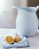 Halved Meyer Lemon Wrapped in Cheesecloth with a Water Pitcher