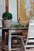Buchsbaum im Übertopf aus Vintage Geflecht neben Blätterzweigen und Kerzenständer auf Holztisch vor Wand mit Holzpaneelen und abblätternder Farbe