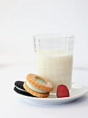 Two Cookies with a Raspberry and a Glass of Milk; On a Plate