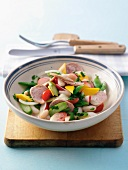 Sausage salad with tomatoes, white beans, green asparagus and radish