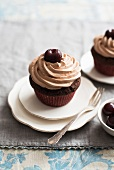 Cherry cupcakes topped with chocolate cream