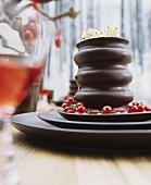 Baumkuchen (German layer cakes) with trusses of redcurrants on a set of dark brown ceramic dishes