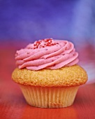 A cupcake topped with raspberry cream