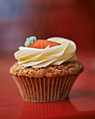 A carrot cupcake topped with cream cheese icing