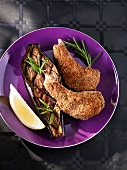 Lamb cutlets with parmesan coating, grilled aubergine and a lemon wedge