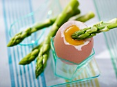 A soft boiled egg with green asparagus