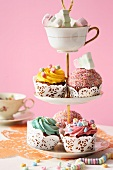 An assortment of cupcakes and marshmallows on a tiered cake stand