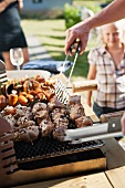 Man grilling meats on barbecue while woman and teen girl watch