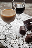 A glass of Baileys and one of Kahlua with assorted filled chocolates to one side