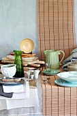 Crockery, wooden chopping boards and table linen in natural colours on a table