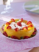A baba topped with strawberries and piped whipped cream