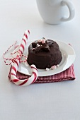 A miniature chocolate torte with a candy cane at Christmas