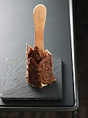 An ice lolly coated with chocolate and chopped nuts