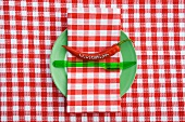 A place setting for an invitation, with a chilli pepper and gingham napkin