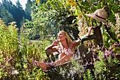 Frau nimmt ein Bad in einem Holzbottich am Brunnen im Garten