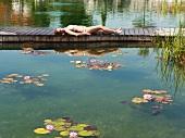 Frau liegt auf dem Holzsteg in einem Naturteich