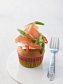 A cupcake topped with cream cheese, wild asparagus, cured ham and chilli slices