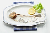 A fish skeleton, a slice of lemon and a lettuce leaf on a plate